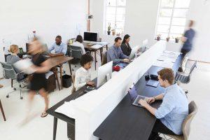 persone a lavoro su scrivanie con pareti divisorie