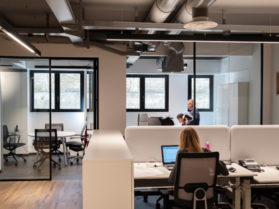 Uffici e scrivanie bianche con ragazza che lavora al computer