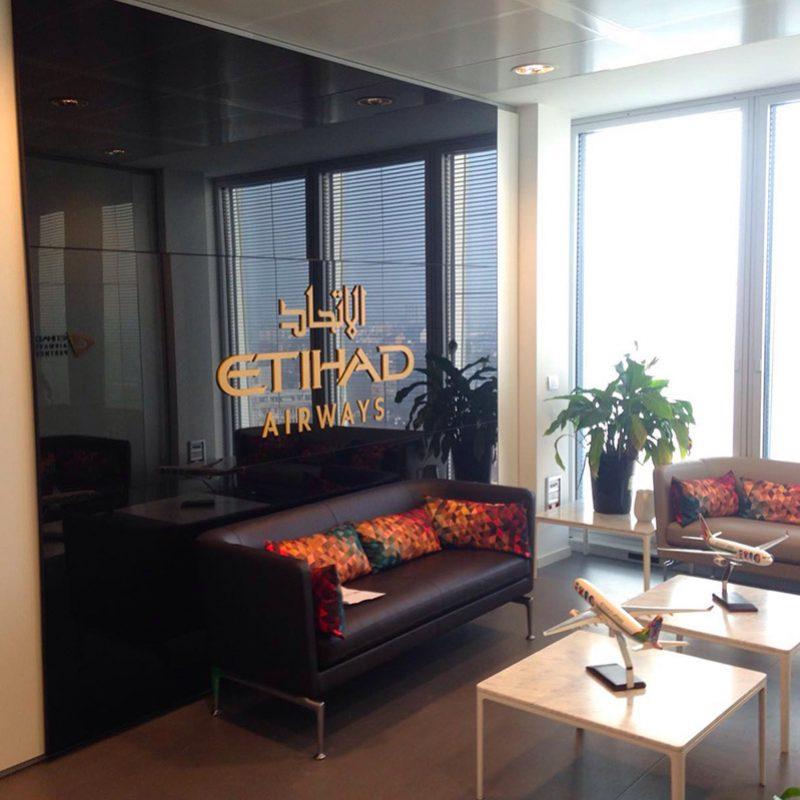 sala accoglienza con divani tavolini e parete con logo etihad airways